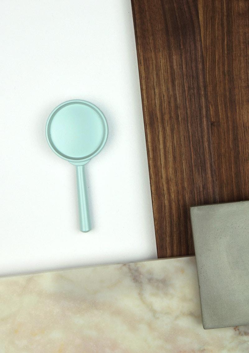Mintfarbene Lupe als Symbol für die Entwicklung von Unternehmensidentitäten