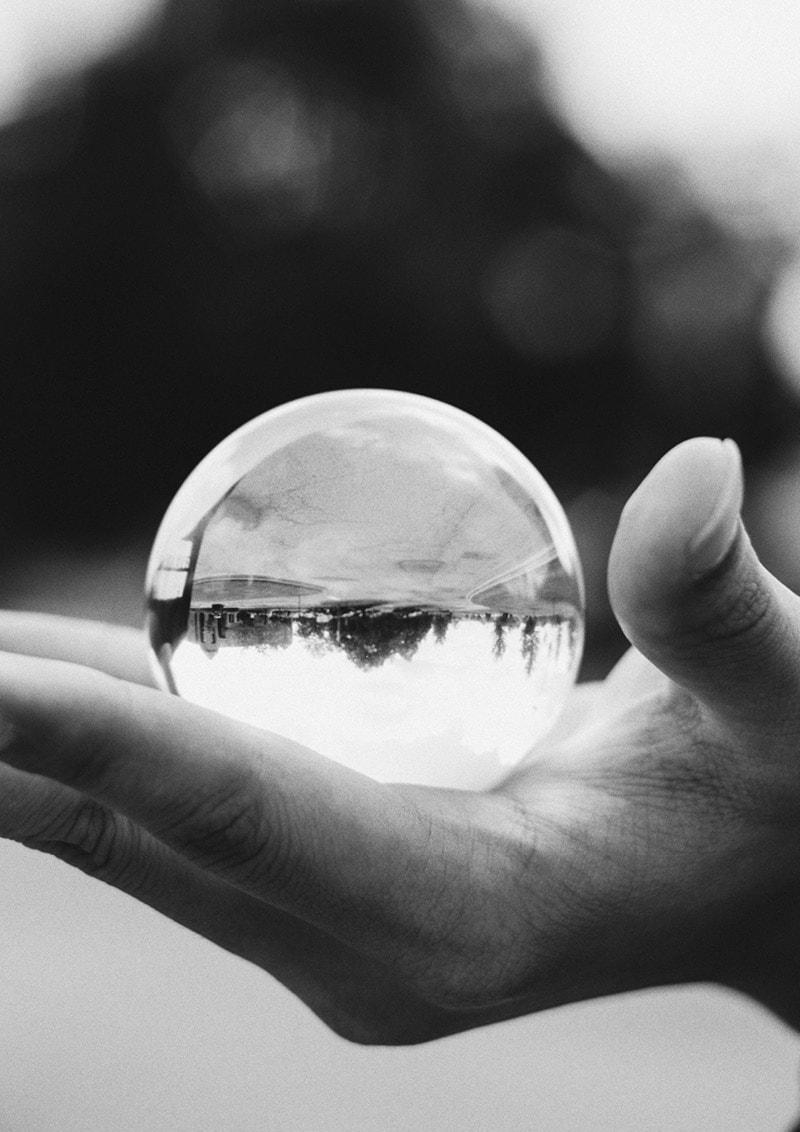 Glaskugel in Hand als Symbol für Konzeptverdichtung